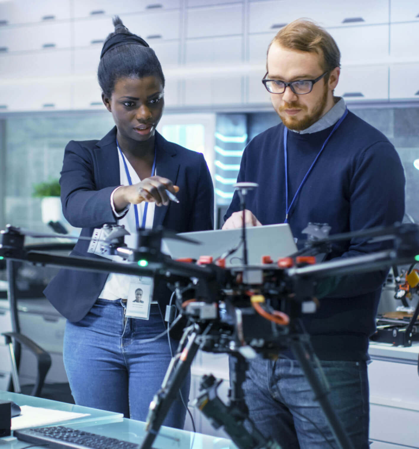 A black woman and Caucasian man working together on a drone in a lab.